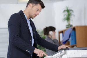 Mann an einem Faxgeraet